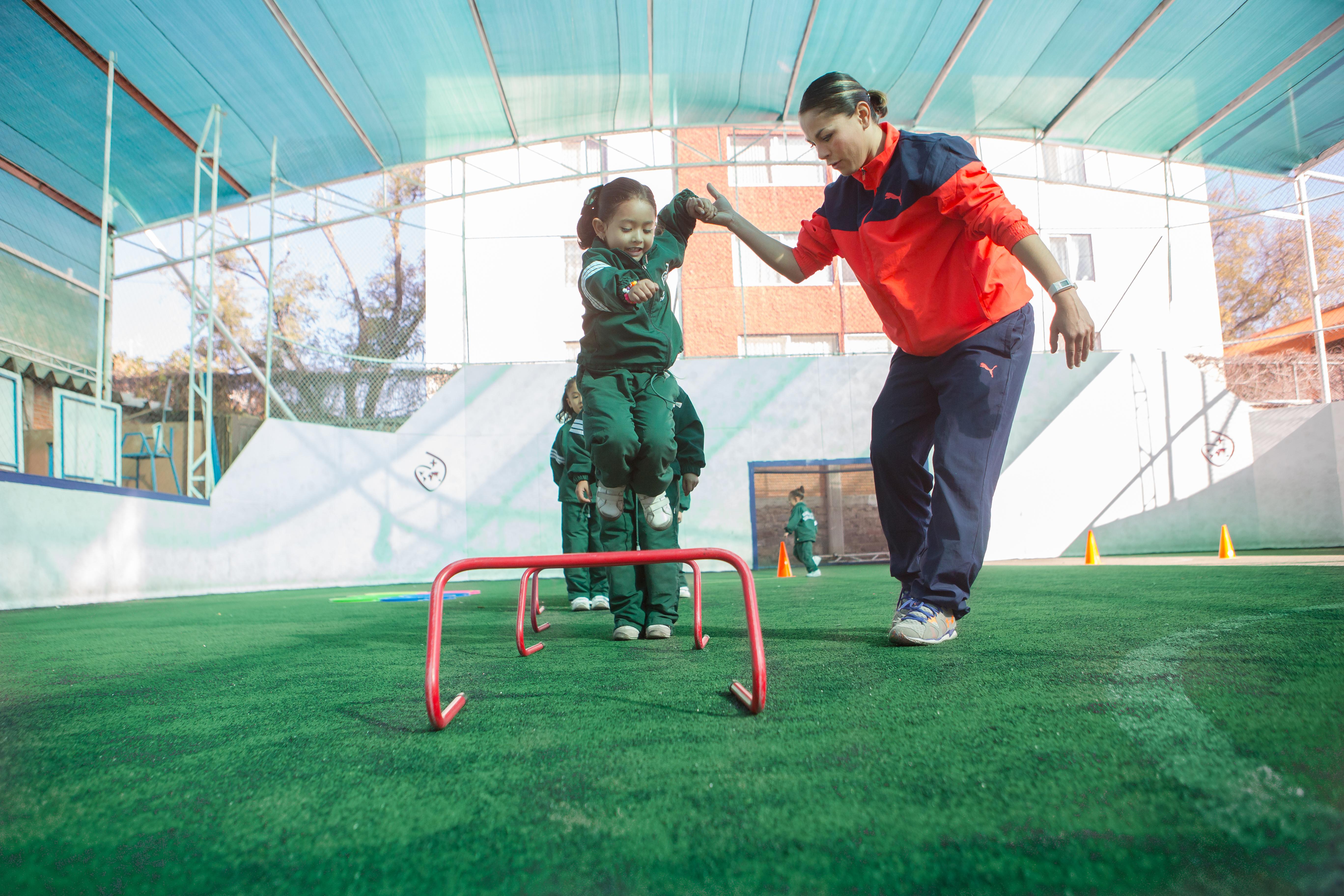 Niña con entrenador en campo de fútbol