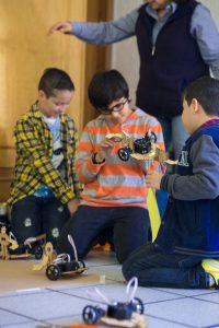Niños de primaria jugando con robots